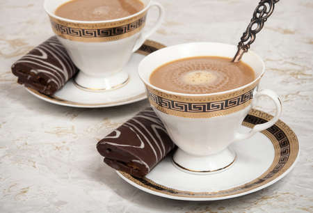 Two cups with the coffee and the chocolate meat loaves. Stock Photo
