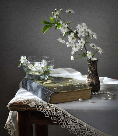 Still life with the book and the efflorescent cherries. photo