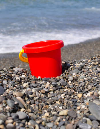 Red pail on the beach in sea.