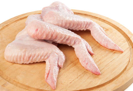 Damp hen wings on the cutting board. Stock Photo