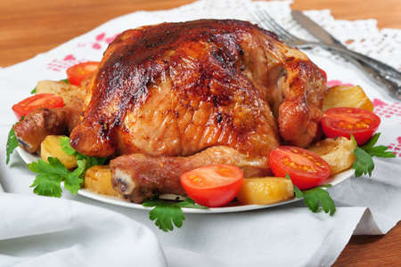 Baked chicken with potatoes and tomatoes. Stock Photo