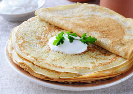 Pancakes with sour cream close up.