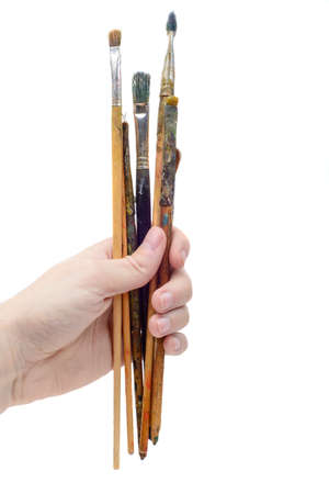 Set of paint brushes in hand of artist isolated on white