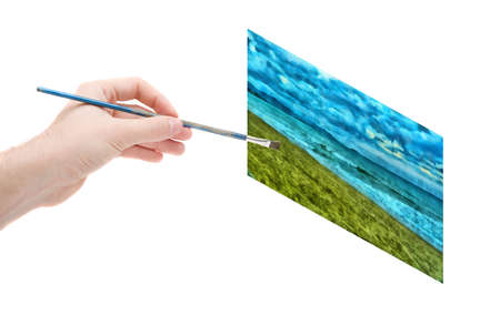 The hand of the artist with a brush draws a picture on the white isolated background photo