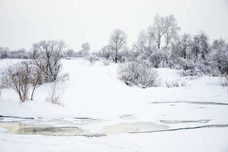 Snowy landscape on the river photo