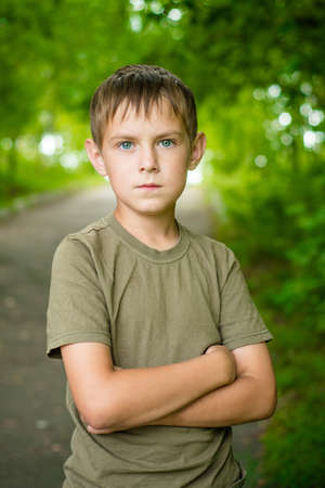 Close-up portrait of serious little boy with folded hands looking at the camera outdoors
