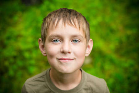 Close-up portrait of smiling little boy looking at the camera outdoors Stock Photo