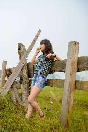 Portrait of pretty brunette standing on farm