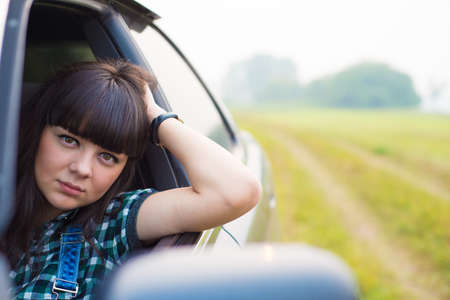 rout: Portrait of pretty brunette sitting in the car