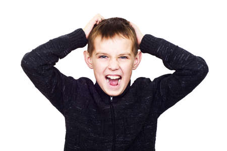 madly: Close-up portrait of boy shouting madly with his hands over his head isolated on white