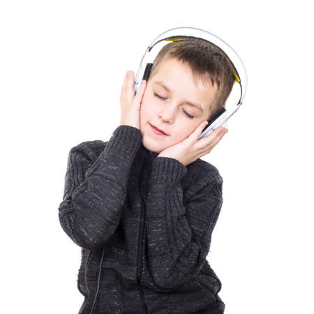 Close up portrait of eyes closed boy listening to music with headphones isolated on white photo