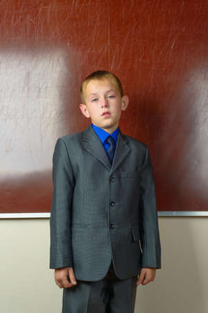 Portrait of schoolboy in classroom standing near the blackboard photo
