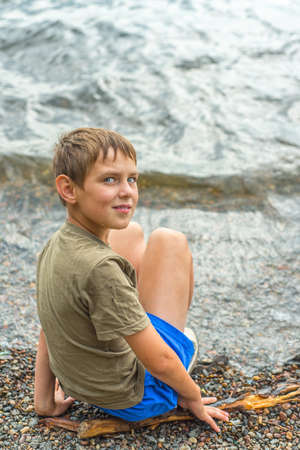 Close-up portrait of serious little boy sitting near the river looking at the camera Stock Photo