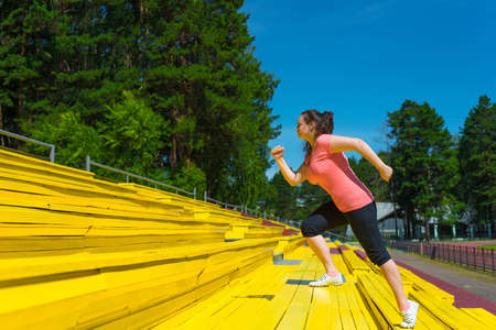 Portrait of single woman doing exercise at the stadium Stock Photo