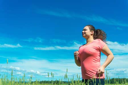 Portrait of single woman jogging in wide field photo
