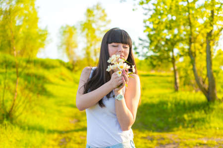 Portrait of happy young girl sniffing the bouquet of flowers in summer field Stock Photo