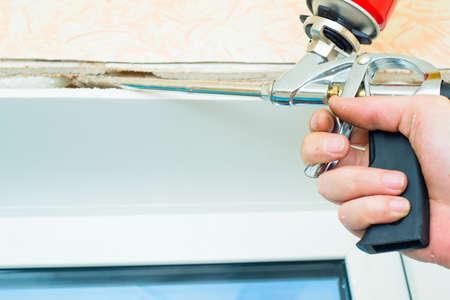 Nail gun being used to install trim around plastic window in doors Stock Photo