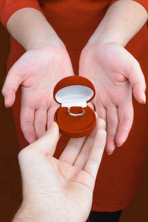 Mans hand giving to her red jewelry box with ring  photo