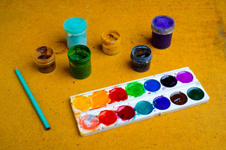 Set of used watercolor and gouache cans of paint on the table