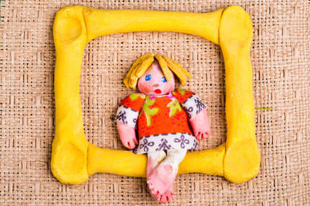 Handmade gypsum doll with yellow frame on straw background photo