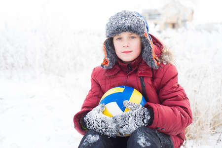 Portrait of a boy in a red jacket sitting in the snow with a volleyball ball