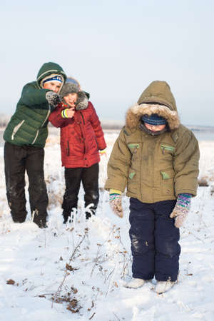 Two boys bully child outdoors in winter sunny day Stock Photo