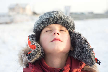 Portrait of a boy close up with her eyes closed in the winter outdoors with blurred background
