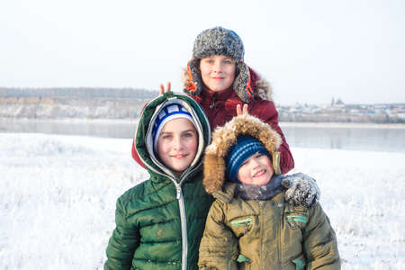 Three boys playing in the snow in the winter outdoors