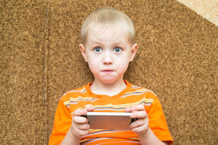 cell phone addiction: Little boy sitting on the couch with surprised eyes and holding a smartphone
