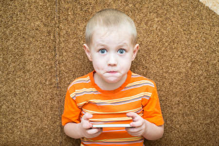 Little boy sitting on the couch with surprised eyes and holding a smartphone