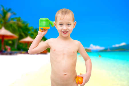 Small boy with toys on the beach