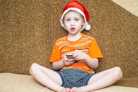 Little boy sitting on the couch with a smartphone in the hat of Santa Claus