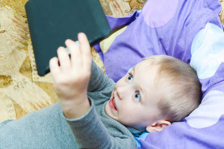 Little boy playing on the couch in the tablet