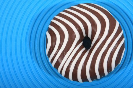 Doughnut with striped chocolate icing from above photo