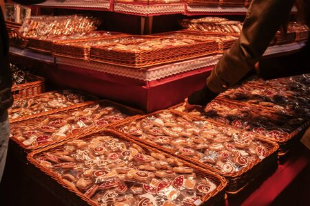 A customer is checking the typical Christmas sweets in a market stall in the streets of Budapest, Hungary - Wicker boxes full of colored gingerbread candies - A greedy holiday concept