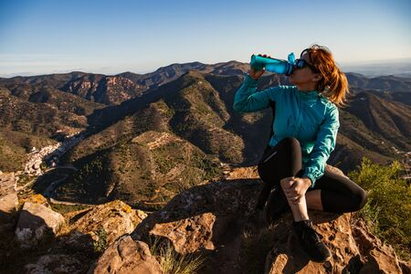 A hiker girl is sitting and drinking fresh water from her blue canteen on the edge of the cliff - She is wearing sunglasses, black leggings and trainers - Solo hiking concept with mountain background