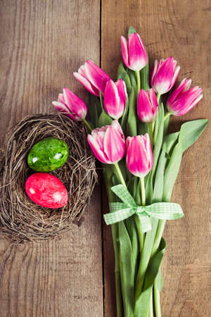 decorated eggs: tulips and decorated eggs in the nest Stock Photo