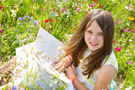 commitment committed: girl reads the book in the field Stock Photo