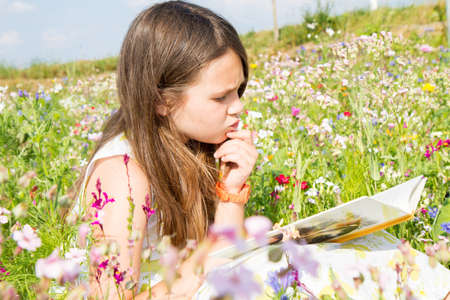 commitment committed: child focused to read the book in the field