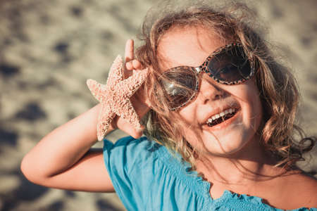 joyous: beautiful girl at the beach with starfish Stock Photo