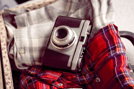 Old photographic camera and suitcase with clothes
