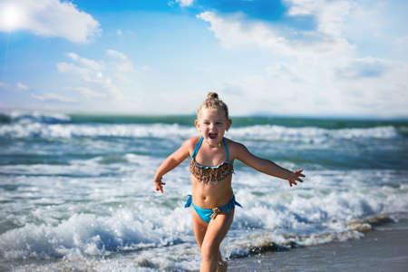 Little girl run on the seashore Imagens