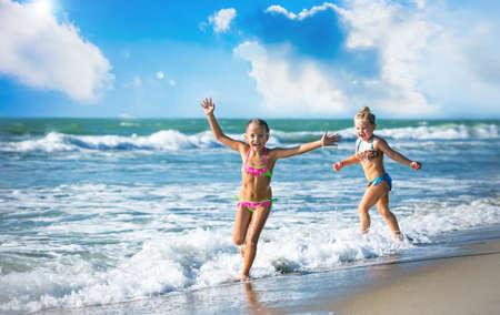 Happy little girls running on the seashore