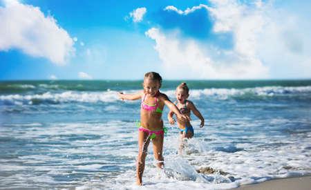 Little girls run on the seashore Imagens