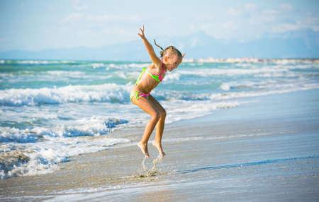 Five years old girl jump on the seashore