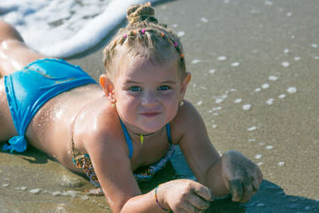 Little girl lying on the seashore