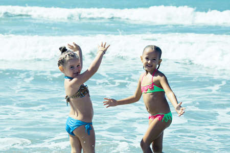 Funny girls play in the water Imagens