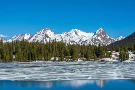 Landscape of melting ice on Molas Lake with forest and snow-covered mountains behind in the San Juan Mountains of Colorado