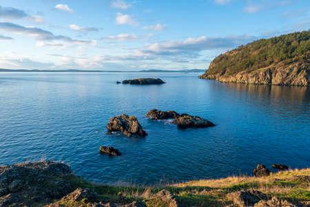 Landscape of sky, ocean, rocks and hills on Fidalgo Island in Washington 写真素材