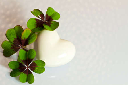 lucky clover: A white heart with lucky clover on white background Stock Photo